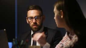 Businessman and businesswoman discussing business project, working late in office. Serious businessman in suit and glasses discussing explaining business project stock footage