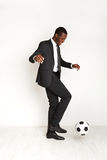 Serious businessman in suit playing football Royalty Free Stock Image