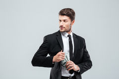 Serious businessman in suit and tie hiding money in pocket Stock Image