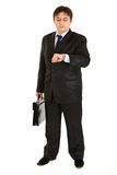 Serious businessman with suitcase looking at watch Stock Photos