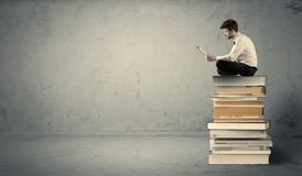 Man with laptop sitting on books Royalty Free Stock Photos