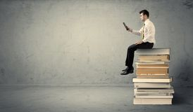 Man with laptop sitting on books. A serious businessman with tablet in hand in suit sitting on a pile of giant books in front of a textured grey wall Royalty Free Stock Photo