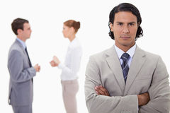 Serious businessman with talking colleagues behind him Royalty Free Stock Image