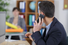 Serious businessman talking on mobile phone with managing director Royalty Free Stock Image