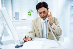 Serious businessman talking on the phone. In his desk Stock Image