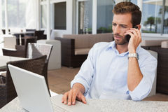 Serious businessman talking on phone using his laptop. In patio of restaurant Royalty Free Stock Photo