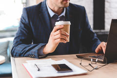 Serious businessman tasting beverage in office Royalty Free Stock Images