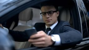 Serious businessman testing new business app on telephone while waiting in car royalty free stock photos