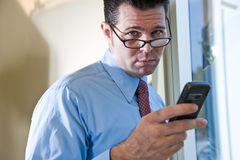 Serious businessman texting on mobile phone Stock Photo