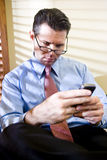 Serious businessman texting on mobile phone Stock Photos