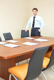 Serious businessman in tie stands near table Stock Photo
