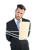 Serious businessman tied up at work Stock Photo