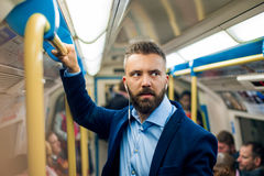 Serious businessman travelling to work. Standing inside undergro Royalty Free Stock Photo