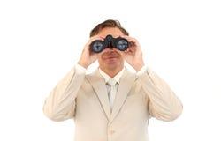 Serious businessman using binoculars Stock Photos