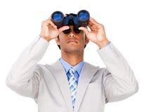 Serious businessman using binoculars Stock Images