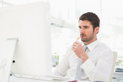 Serious businessman using computer monitor Stock Photography