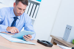 Serious businessman using digital tablet Royalty Free Stock Photos