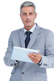 Serious businessman using digital tablet Royalty Free Stock Images