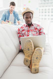 Serious businessman using laptop on couch Royalty Free Stock Images