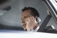 Serious Businessman Using Mobile Phone In Car]] Stock Photo