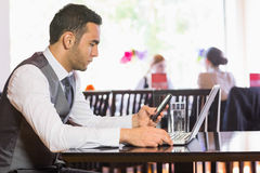Serious businessman using phone while working on laptop stock images