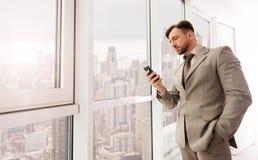 Serious businessman using smartphone Stock Photo