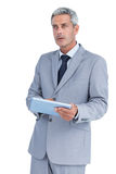 Serious businessman using tablet pc looking away Stock Image