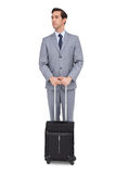 Serious businessman waiting with his luggage Royalty Free Stock Photos
