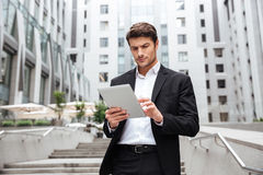 Serious businessman walking and using tablet in the city Royalty Free Stock Photography
