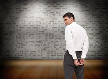 Serious businessman wearing handcuffs Royalty Free Stock Photography