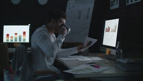 Serious businessman working on computer in night office. stock video footage