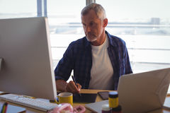 Serious businessman working on digitizer at office desk Royalty Free Stock Images