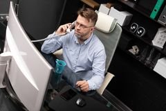 Serious Businessman working in office at computer Desk and talking on landline. Representative man with facial hair in gray shirt and jeans works in modern royalty free stock photos