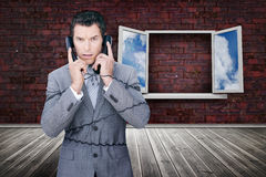 Serious businessman wrapped in cables phoning Royalty Free Stock Photos