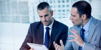 Serious businessmen analyzing documents on their tablet Royalty Free Stock Image