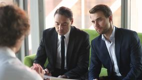 Serious businessmen employers listening talking to applicant at job interview