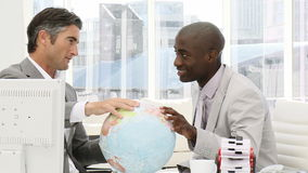Serious businessmen looking at a terrestrial globe Stock Photo