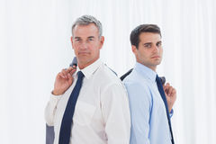 Serious businessmen posing back to back together. In bright office Stock Photography