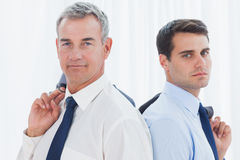 Serious businessmen posing back to back together while holding t. Serious businessmen in bright office posing back to back together while holding their jacket Stock Photography