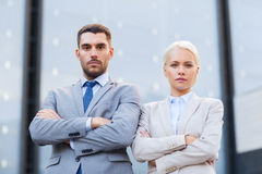 Serious businessmen standing over office building Stock Photo