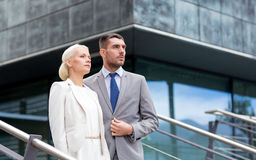 Serious businessmen standing over office building Royalty Free Stock Images