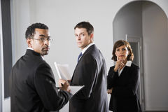 Serious businesspeople looking over shoulder Royalty Free Stock Photos