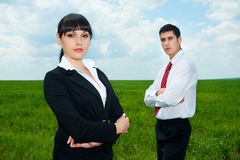 Serious businesspeople standing on green meadow Stock Photos