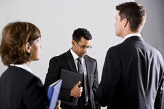 Serious businesspeople, standing, looking down Stock Images