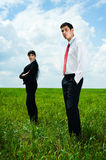 Serious businesspeople standing on meadow Stock Images