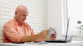 Serious businessperson at home office reading newspaper in front of his laptop.  stock footage