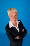 Serious businesswoman. Half body portrait of serious businesswoman with arms folded and white hair; blue studio background Stock Image