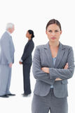 Serious businesswoman with arms folded and colleagues behind her Stock Photos