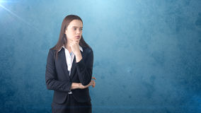 Serious businesswoman with arms folded looking at you. Standing over brown background. Royalty Free Stock Photo