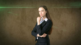 Serious businesswoman with arms folded looking at you. Standing over brown background. Royalty Free Stock Photos